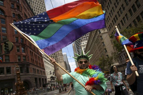 A man dressed as the Statue of Liberty carries a rianbow American flag while marching in a gay pride parade in San Francisco, California June 28, 2015. REUTERS/Elijah Nouvelage